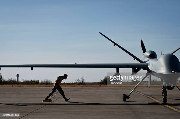 In this handout provided by the US Air Force after taxiing in an MQ9 Reaper Airman 1st Class Jon Mann walks under a Reaper's wing to place wheel...