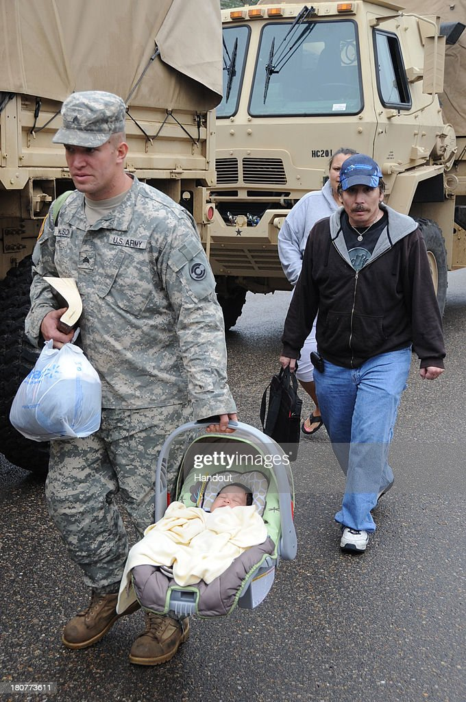 In this handout provided by the U.S. National Guard, Colorado Army National Guard Sgt. David Wilson, 1st Battalion 157th Forward Support Company, escorts Thomas Walter and Melinda Villa while carrying Ezra Villa to the flood evaluation area September 13, 2013 in Lyons, Colorado. Heavy rains for the better part of week fueled widespread flooding in numerous Colorado towns. The historic flooding forced thousands to evacuate the area and more rain is predicted through the weekend.