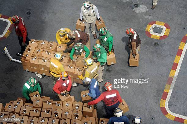 In this handout provided by the US Navy Air department Sailors stack relief supplies on the flight deck of the US Navy's forwarddeployed aircraft...