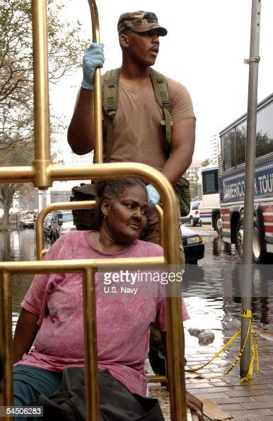 In this handout provided by the US Navy an Army National Guard Solider helps an injured New Orleans citizen prior to helping her into a waiting bus...