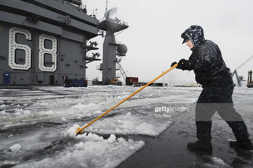 In this handout provided by the US Navy Aviation Boatswain Mate Airman Tatyana Sakara removes snow from the flight deck of the aircraft carrier USS...