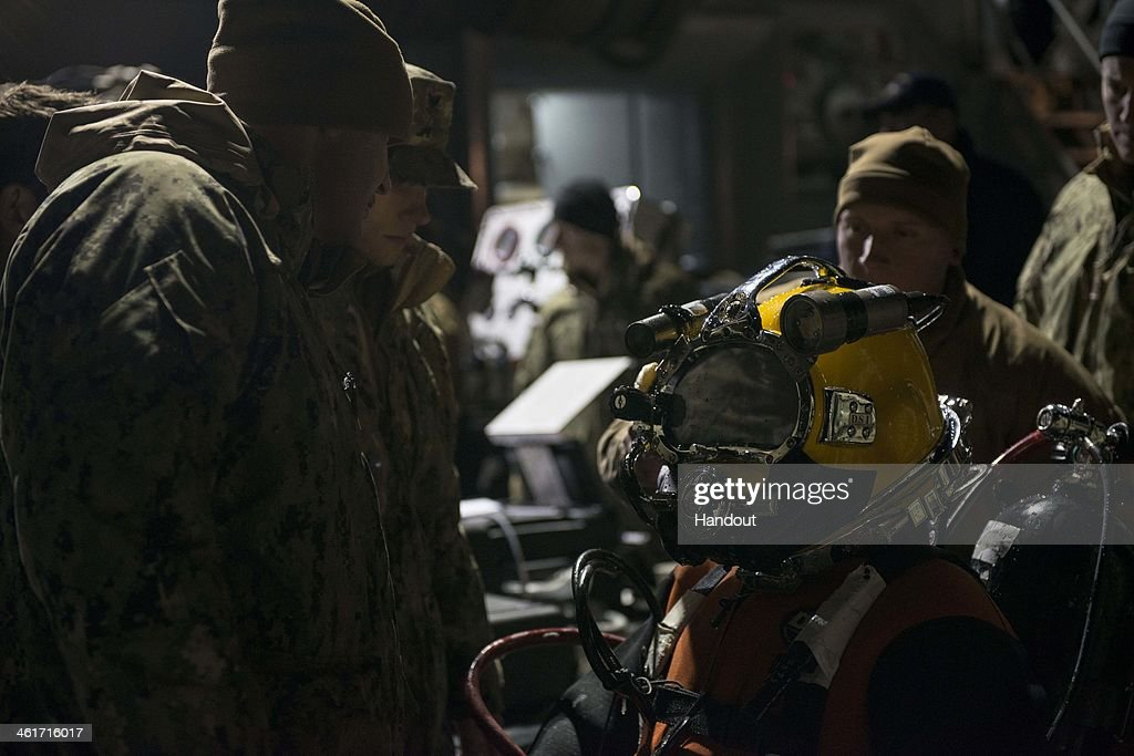 In this handout provided by the U.S. Navy, Navy Diver 2nd Class Ben Eisenbarth, assigned to Mobile Diving and Salvage Unit (MDSU) 2, Company 2-2, receives dive supervisor checks before entering the water on January 9, 2014 in the Atlantic Ocean. MDSU-2 is underway aboard the Military Sealift Command rescue and salvage ship USNS Grasp (T-ARS-51) searching for the missing crew member of an MH 53E Sea Dragon helicopter that went down Jan. 8. 2014 off the coast of Virginia. (Photo by Wyatt Huggett/U.S. Navy via Getty Images