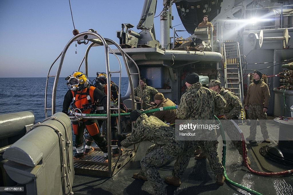 In this handout provided by the U.S. Navy, Navy divers assigned to Mobile Diving and Salvage Unit (MDSU) 2, Company 2-2, are lowered into the water from the Military Sealift Command rescue and salvage ship USNS Grasp (T-ARS-51)on January 9, 2014 in the Atlantic Ocean. MDSU-2 is underway aboard the Military Sealift Command rescue and salvage ship USNS Grasp (T-ARS-51) searching for the missing crew member of an MH 53E Sea Dragon helicopter that went down Jan. 8. 2014 off the coast of Virginia. (Photo by Wyatt Huggett/U.S. Navy via Getty Images
