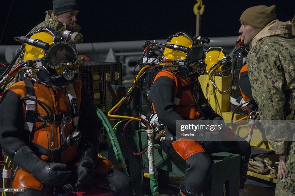 In this handout provided by the U.S. Navy, Navy Divers assigned to Mobile Diving and Salvage Unit (MDSU) 2, Company 2-2, listen to a pre-dive briefing before entering the water on January 9, 2014 in the Atlantic Ocean. MDSU-2 is underway aboard the Military Sealift Command rescue and salvage ship USNS Grasp (T-ARS-51) searching for the missing crew member of an MH 53E Sea Dragon helicopter that went down Jan. 8. 2014 off the coast of Virginia. (Photo by Wyatt Huggett/U.S. Navy via Getty Images