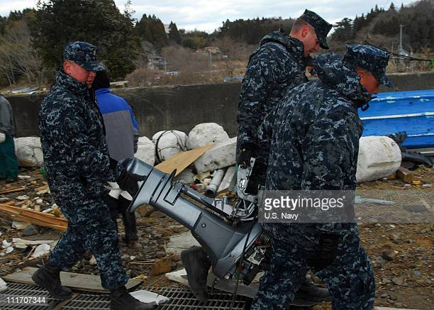 In this handout provided by the US Navy sailors attached to the forwarddeployed amphibious assault ship USS Essex move a boat motor from a harbor...