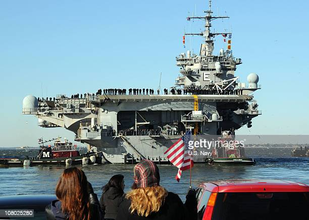 In this handout provided by the US Navy Sailors man the rails aboard the aircraft carrier USS Enterprise while family and friends wave goodbye as the...