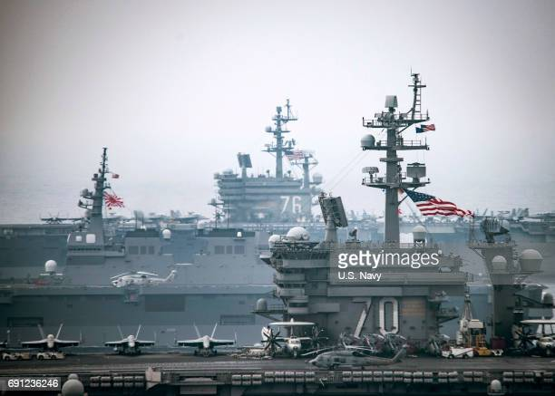 In this handout provided by the US Navy The Carl Vinson Carrier Strike Group including the aircraft carrier USS Carl Vinson operate with the Ronald...