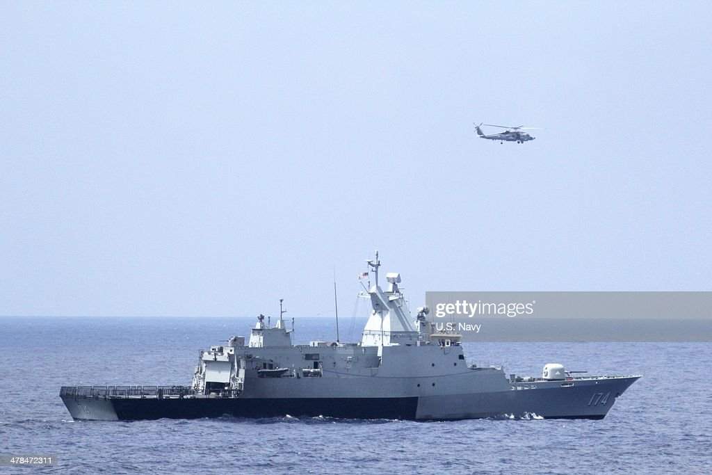 In this handout provided by the US Navy the Royal Malaysian Navy corvette KD Terengganu and a US Navy MH60R Sea Hawk helicopter from the Blue Hawks...