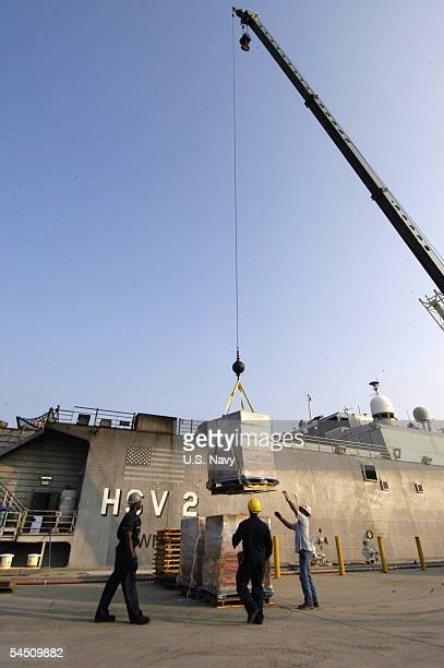 In this handout provided by the US Navy US Navy Sailors and civilian workers unload relief supplies from the US Navy High Speed Vessel Swift on board...
