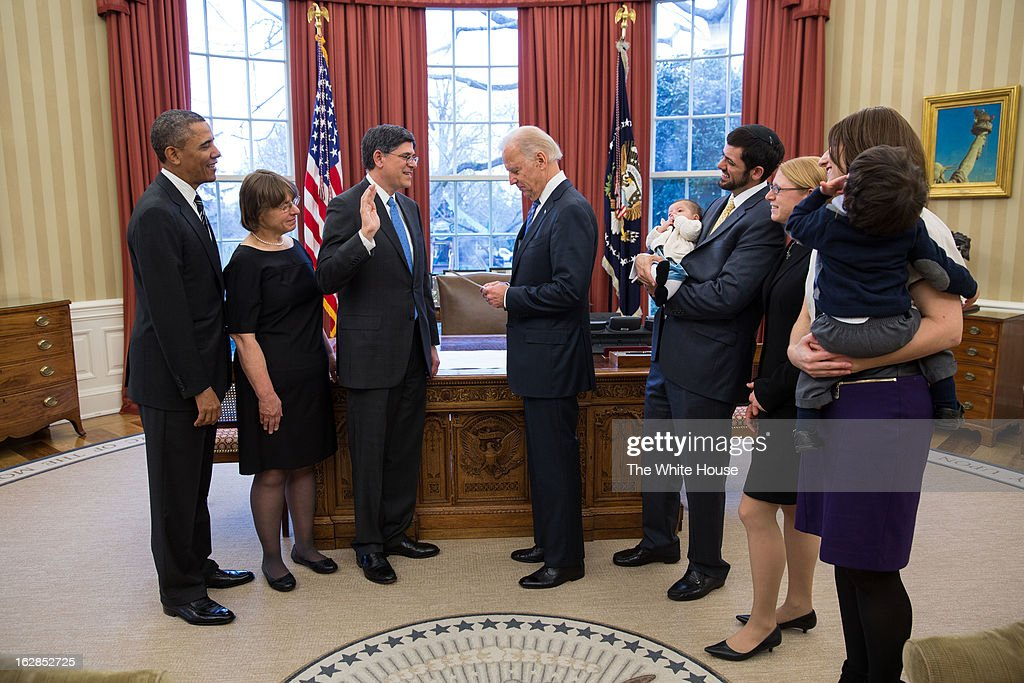 In this handout provided by the White House, President Barack Obama (L) watches as Vice President Joe Biden (4L) swears in Treasury Secretary Jack Lew (3L) during a ceremony in the Oval Office February 28, 2013 in Washington, DC. Lew's family (L-R), wife Ruth Schwartz, granddaughter Eliora Lew, son Danny Lew, daughter Shoshana Lew, daughter-in-law Zahava Lew, and grandson Moshe Lew, were in attendance.