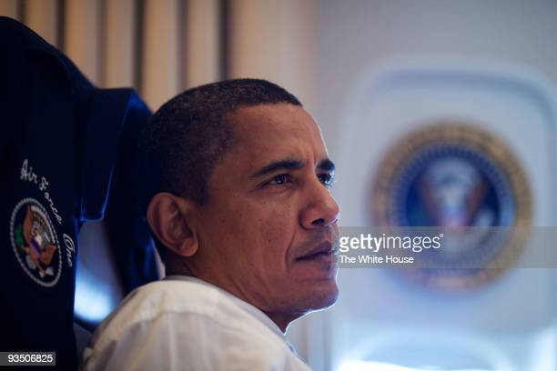In this handout provided by the White House President Barack Obama listens during a meeting with aides on Air Force One November 16 2009 en route to...