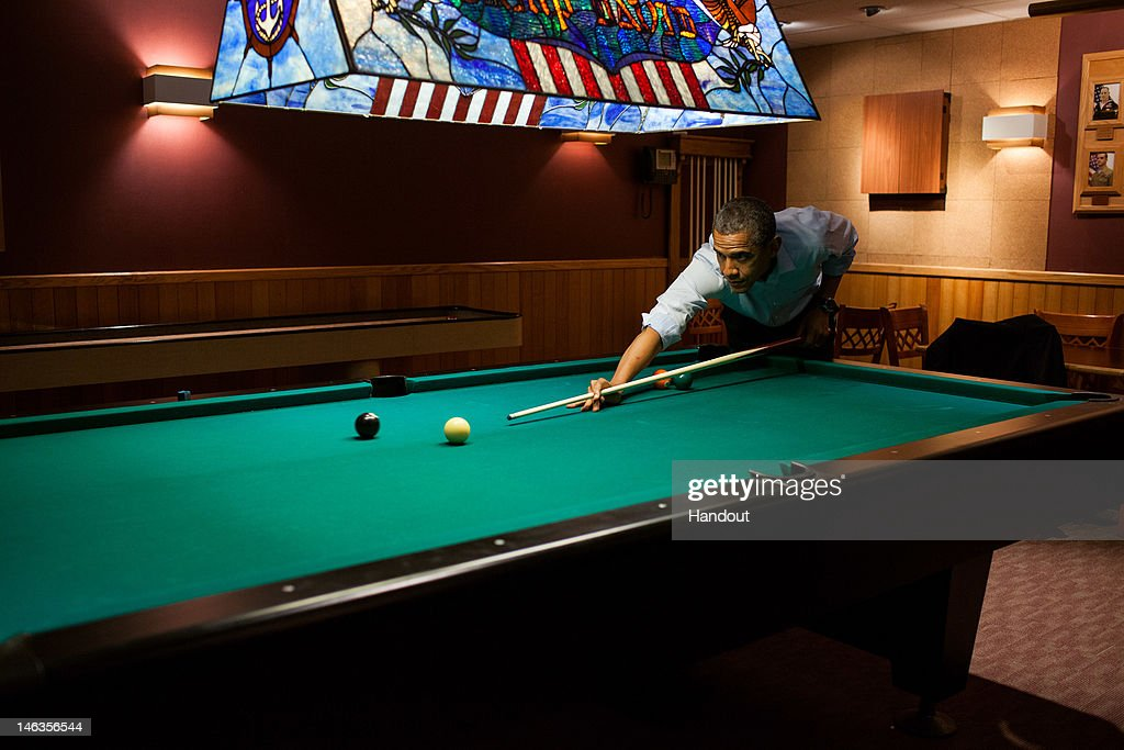 In this handout provided by the White House, U.S. President Barack Obama plays a game of pool in the Holly Cabin following the conclusion of the G8 Summit on May 19, 2012 in Camp David, Maryland.