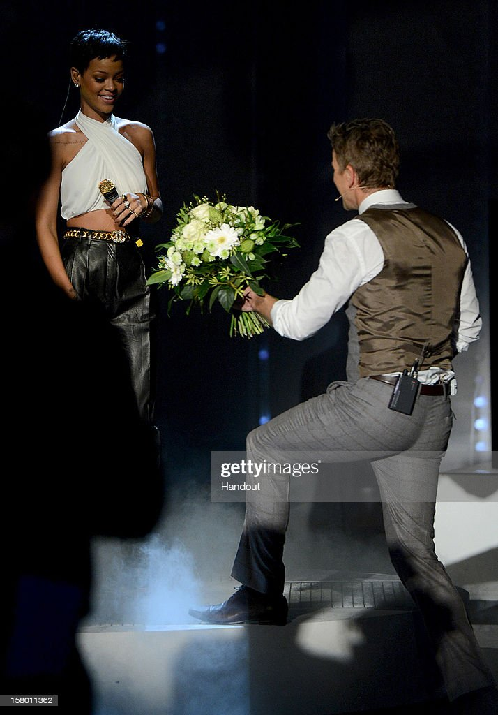In this handout provided by the ZDF, Markus Lanz presents flowers to Rihanna at 'Wetten dass..?' From Freiburg on December 8, 2012 in Freiburg im Breisgau, Germany.