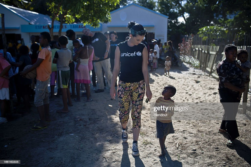 In this handout provided by UNICEF, UNICEF supporter <a gi-track='captionPersonalityLinkClicked' href=/galleries/search?phrase=Katy+Perry&family=editorial&specificpeople=599558 ng-click='$event.stopPropagation()'>Katy Perry</a> walks with a small boy she has just met, during her visit to the Tamatave Youth Centre in the city of Tamatave on April 6, 2013 in Atsinanana Region, Madagascar. The centre supports recreational activities for adolescents. From 4 to 6 April 2013 in Madagascar, internationally acclaimed American singer/songwriter and UNICEF supporter <a gi-track='captionPersonalityLinkClicked' href=/galleries/search?phrase=Katy+Perry&family=editorial&specificpeople=599558 ng-click='$event.stopPropagation()'>Katy Perry</a> visited UNICEF programmes in health, nutrition, water, sanitation and hygiene, education, child protection and youth development. The visit helped to focus attention on the situation of children in the country, one of the poorest in the world that is still recovering from a political crisis and an ensuing coup in 2009. Currently, some 82 per cent of Malagasies are unable to afford basic needs and services, including food and healthcare. Rates of under-five mortality have decreased but are still unacceptably high, with preventable conditions, such as malaria, diarrhoeal diseases and respiratory infections, causing the majority of deaths. Fully half of the country's children are stunted from chronic malnutrition, a condition that causes often lifelong physical and mental impairment. Maternal mortality, also high, takes the lives of eight women each day. Severely limited access to safe drinking water and improved sanitation facilities, the increased frequency and intensity of natural disasters, and declining public funding for education are also impeding the ability of Malagasy children to survive and thrive. UNICEF has appealed for over US$14.9 million to support addressing these shortfalls throughout 2013.