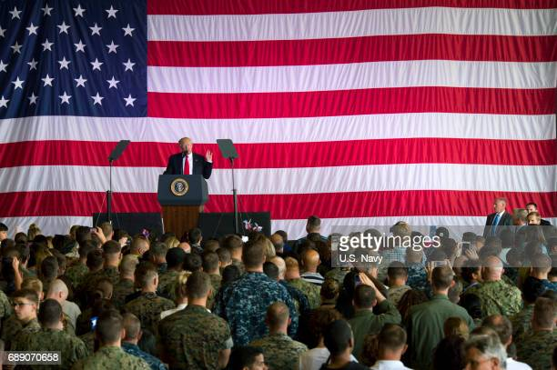 In this handout provided by US Navy President Donald J Trump speaks to service members and their families at Naval Air Station Sigonella during an...