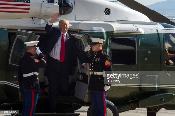 In this handout provided by US Navy President Donald J Trump waves as he exits Marine One at Naval Air Station Sigonella prior to an allhands call...