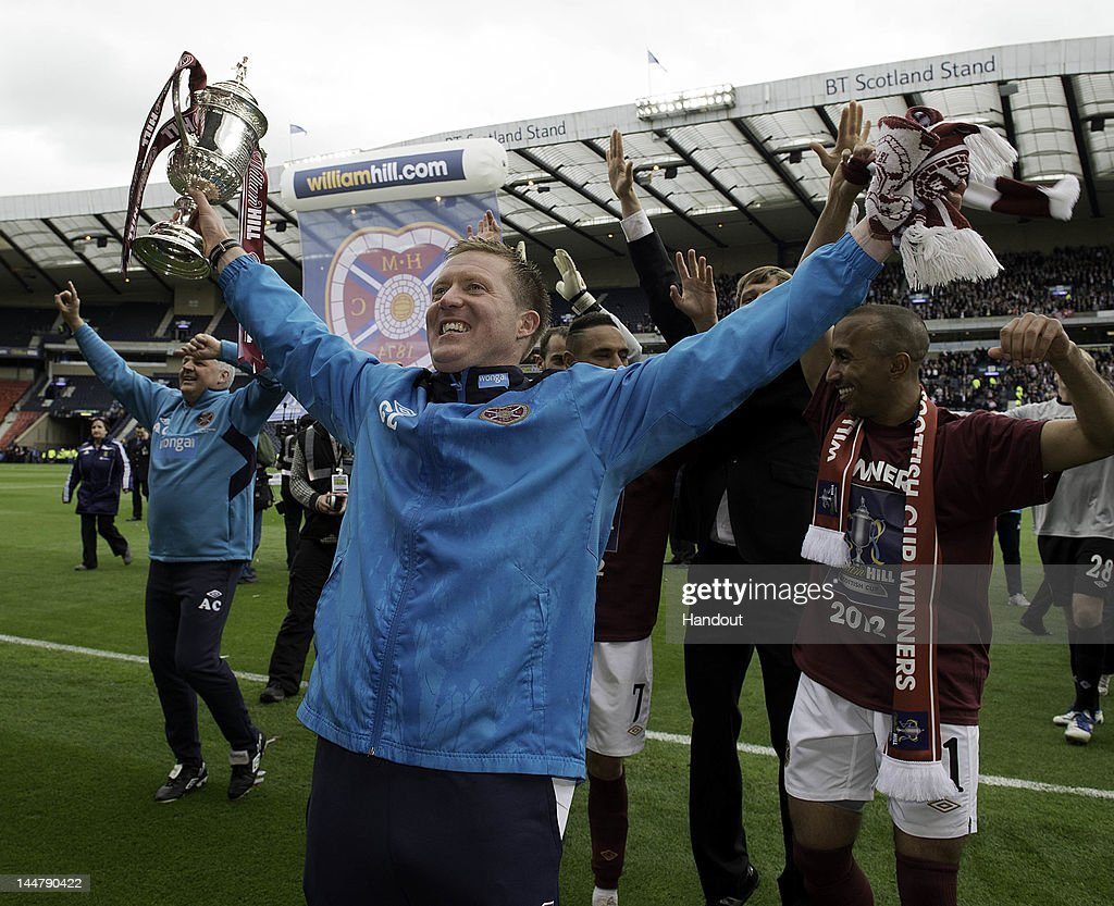 In this handout provided by William Hill, Gary Locke of Hearts celebrates with the cup after winning the William Hill Scottish Cup Final between Hibernian and Hearts at Hampden Park on May 19, 2012 in Glasgow, Scotland.