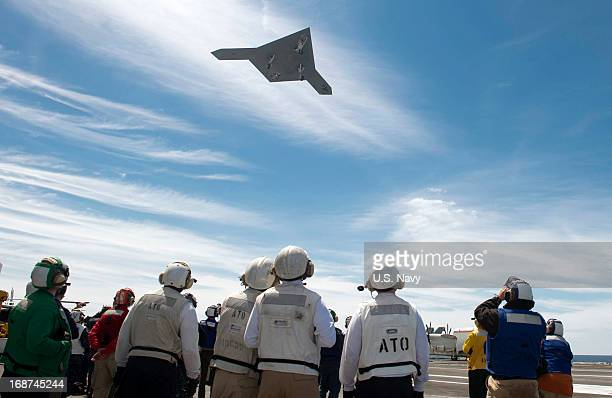 In this handout released by the US Navy An X47B Unmanned Combat Air System demonstrator flies over the flight deck of the aircraft carrier USS George...