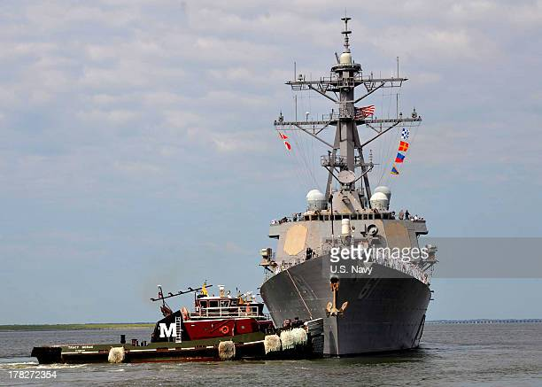 In this handout released by the US Navy the US Navy guidedmissile destroyer USS Ramage is assisted by a tug boat as it pulls away from the pier at...