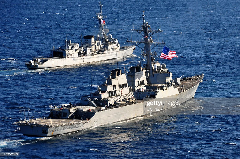 In this handout released by the US Navy the US Navy guidedmissile destroyer USS Barry pulls into formation with the French Marine Nationale...