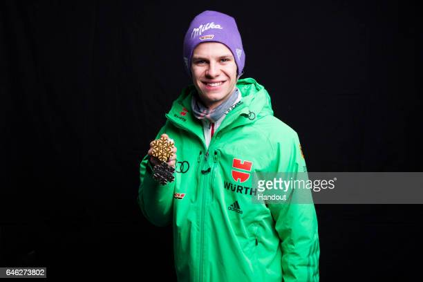 In this handout supplied by NordicFocus Andreas Wellinger of Germany poses with his gold and silver medals after the medal ceremony for the Mixed...