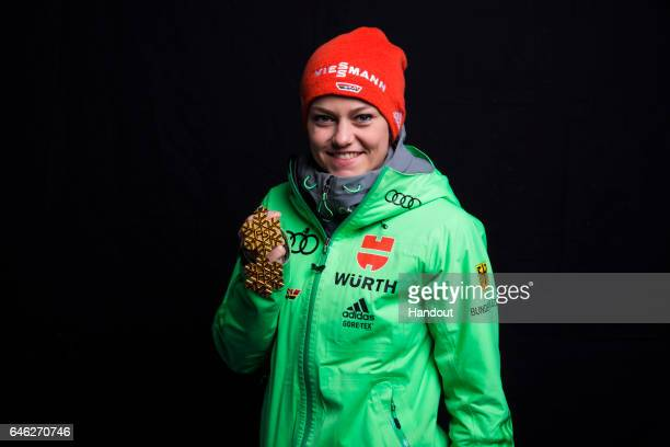 In this handout supplied by NordicFocus Carina Vogt of Germany poses with her two gold medals after the medal ceremony for the Mixed Team Ski Jumping...