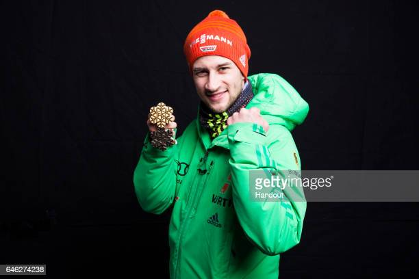 In this handout supplied by NordicFocus Markus Eisenbichler of Germany poses with his gold and bronze medals after the medal ceremony for the Mixed...