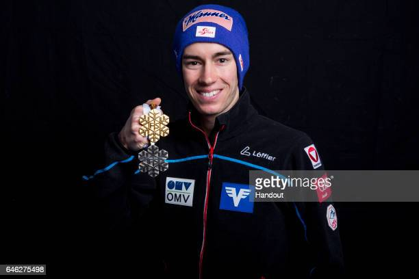 In this handout supplied by NordicFocus Stefan Kraft of Austria poses with his gold and silver medals after the medal ceremony for the Mixed Team Ski...