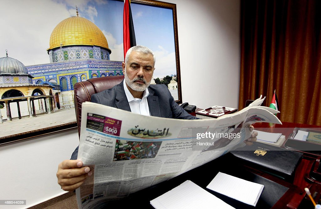 In this handout supplied by the Palestinian Prime Minister's Office (PPMO), Palestinian Prime Minister Ismail Haniyeh reads a newspaper in his office on May 7, 2014 in Gaza.