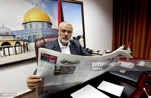 In this handout supplied by the Palestinian Prime Minister's Office Palestinian Prime Minister Ismail Haniyeh reads a newspaper in his office on May...