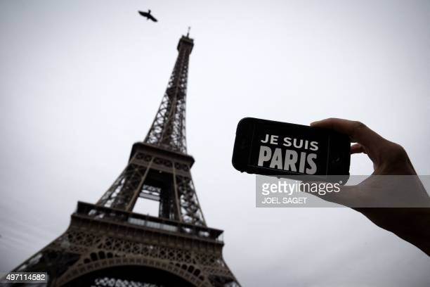 In this illustration picture taken in Paris on November 14 2015 a person holds aloft a smartphone bearing the message 'Je Suis Paris' in front of the...