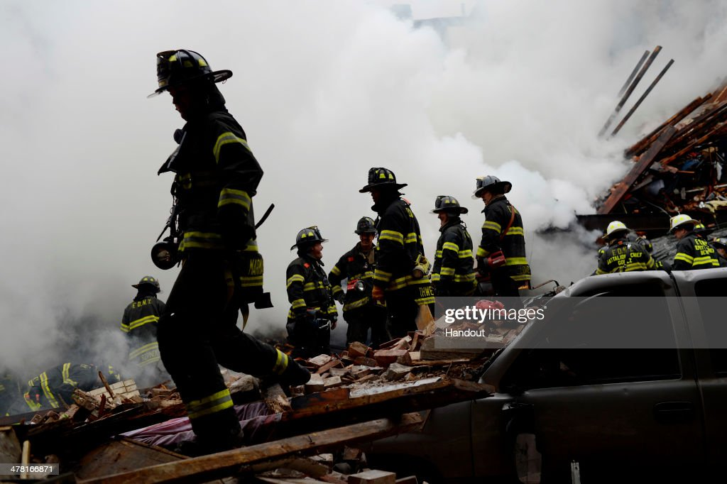 In this image handout provided by the Office of Mayor of New York, firefighters from the Fire Department of New York (FDNY) walk in the rubble as they respond to a five-alarm fire and building collapse at 1646 Park Ave in the Harlem neighborhood of Manhattan March 12, 2014 in New York City. Reports of an explosion were heard before the collapse of two multiple-dwelling buildings at East 116th St. and Park Avenue that left at least 17 injured and a number of people are missing.