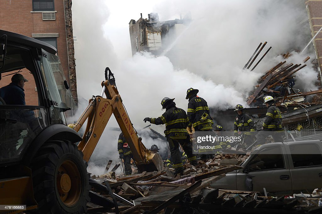 In this image handout provided by the Office of Mayor of New York, firefighters from the Fire Department of New York (FDNY) use an excavator to remove rubble as they respond to a five-alarm fire and building collapse at 1646 Park Ave in the Harlem neighborhood of Manhattan March 12, 2014 in New York City. Reports of an explosion were heard before the collapse of two multiple-dwelling buildings at East 116th St. and Park Avenue that left at least 17 injured and a number of people are missing.