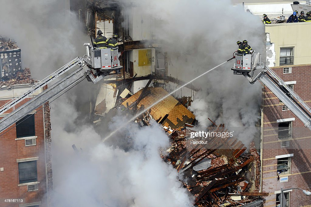 In this image handout provided by the Office of Mayor of New York, firefighters from the Fire Department of New York (FDNY) pour water on the rubble as they respond to a five-alarm fire and building collapse at 1646 Park Ave in the Harlem neighborhood of Manhattan March 12, 2014 in New York City. Reports of an explosion were heard before the collapse of two multiple-dwelling buildings at East 116th St. and Park Avenue that left at least 17 injured and a number of people are missing.
