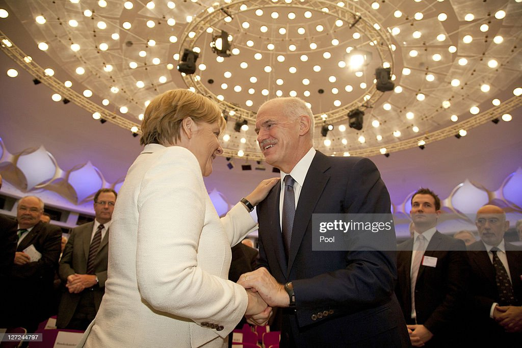 In this image provided by the German press office, German Chancellor Angela Merkel and Greek Prime Minister George Papandreou shake hands during a convention of the Federation of German Industry (BDI), where Papandreou spoke in an appeal for more German investment in Greece, on September 27, 2011 in Berlin, Germany. Papandreou and Merkel are scheduled to meet at the Chancellery later in the day to discuss the current Greek debt crisis that is threatening the stability of the Euro.