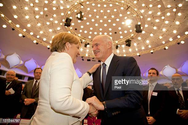 In this image provided by the German press office German Chancellor Angela Merkel and Greek Prime Minister George Papandreou shake hands during a...