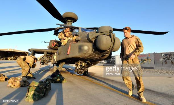 In this image released on January 21 Prince Harry does a preflight check of his Apache Helicopter after starting his 12 hour VHR shift at the British...