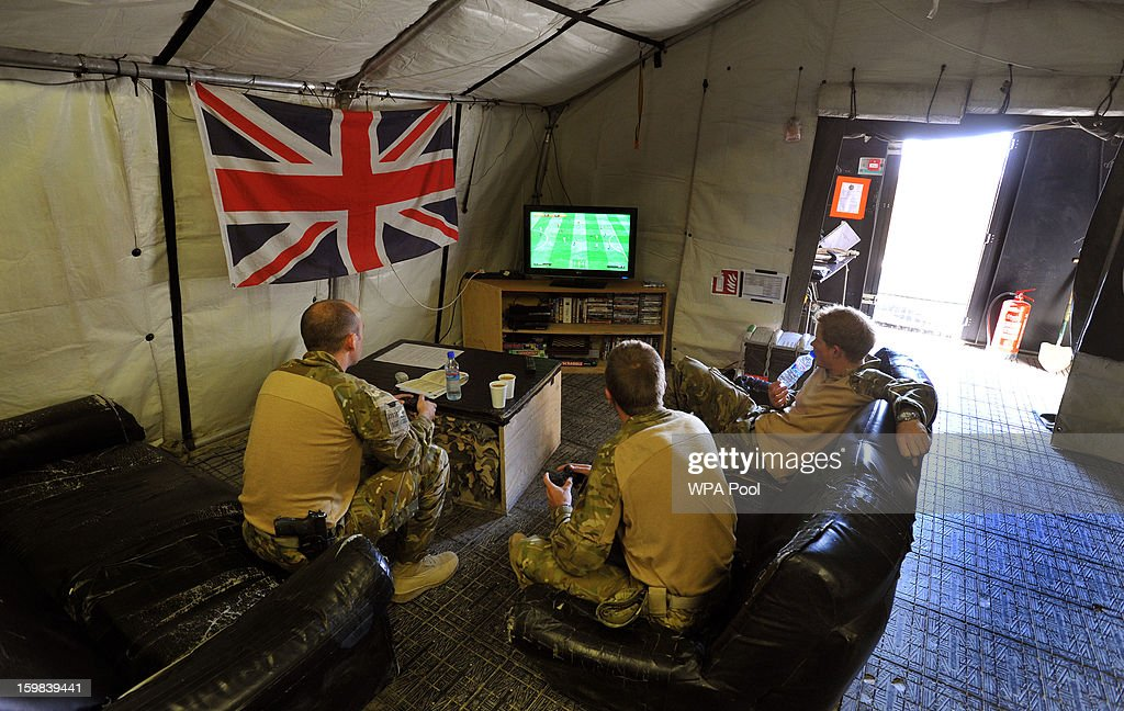 In this image released on January 21 Prince Harry relaxes during a computer football game with fellow Apache Helicopter crew members during their 12...