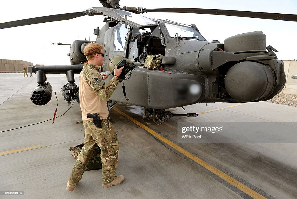 In this image released on January 21, 2013, Prince Harry stands by an Apache helicopter at the British controlled flight-line in Camp Bastion southern Afghanistan. Prince Harry has served as an Apache Helicopter Pilot/Gunner with 662 Sqd Army Air Corps, from September 2012 for four months until January 2013.