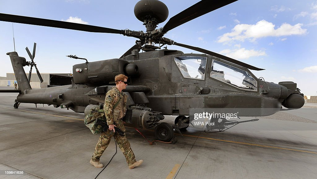In this image released on January 21, 2013, Prince Harry walks past an Apache helicopter at the British controlled flight-line in Camp Bastion in October 31, 2012 in Afghanistan. Prince Harry has served as an Apache Helicopter Pilot/Gunner with 662 Sqd Army Air Corps, from September 2012 for four months until January 2013.