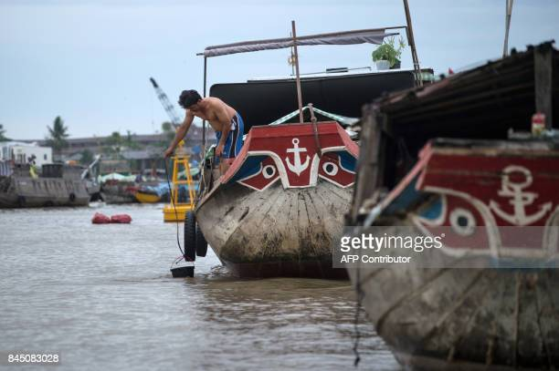 In this July 17 2017 photograph a resident of a house boat lifts a bucket of water in a canal off the Song Hau river at the floating Cai Rang market...