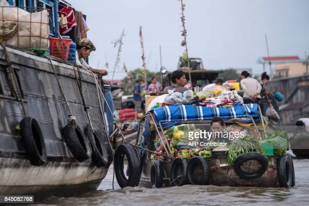 In this July 17 2017 photograph a vendor prepares vegetables that she sold to a resident of a house boat in a canal off the Song Hau river in the...