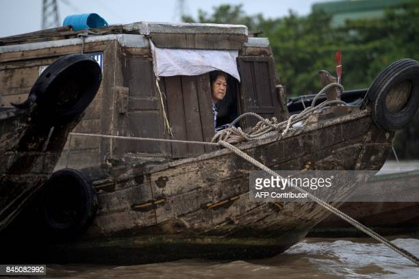In this July 17 2017 photograph a woman looks out from her boat in a canal off the Song Hau river in the floating Cai Rang market in Can Tho a small...