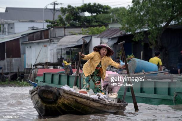 In this July 17 2017 photograph a woman making a living from selling food and drinks from her boat rows in search of customers in a canal off the...