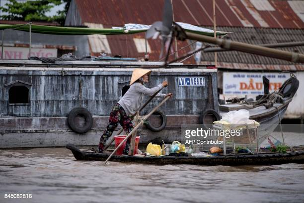 In this July 17 2017 photograph a woman making a living from selling bread and other food and drinks from her boat rows in search of customers in a...