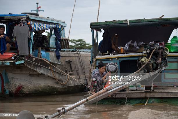 In this July 17 2017 photograph a woman washes clothes from the back of a boat in a canal off the Song Hau river at the floating Cai Rang market in...