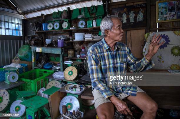 In this July 17 2017 photograph scales repairman Nguyen Van Ut sits inside his house boat in a canal off the Song Hau river in the floating Cai Rang...