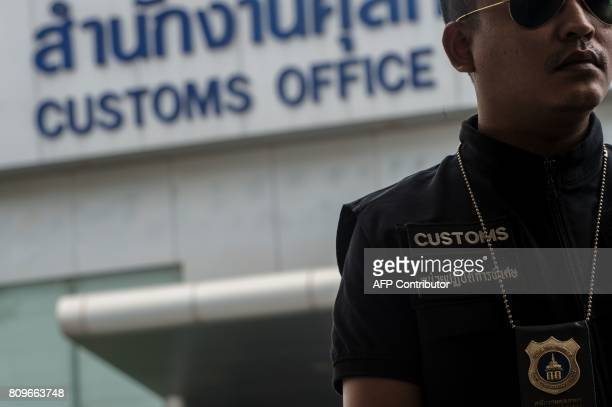 In this June 30 2017 photograph a Thai customs agent stands near luxury cars confiscated at a special Free Trade Zone in Bangkok Thailand's role in...