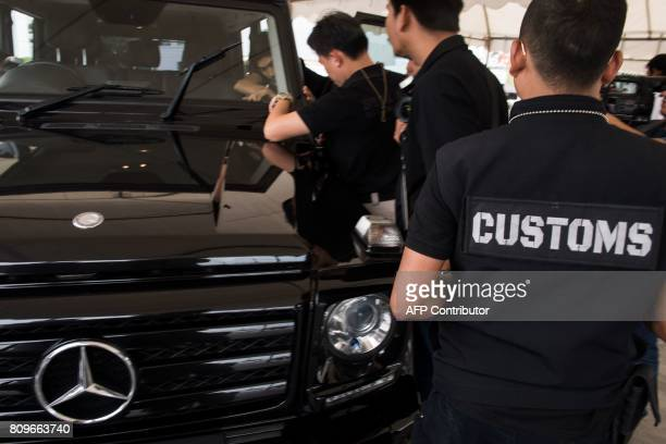 In this June 30 2017 photograph Thai customs agents inspect a luxury vehicle they confiscated at a special Free Trade Zone in Bangkok Thailand's role...