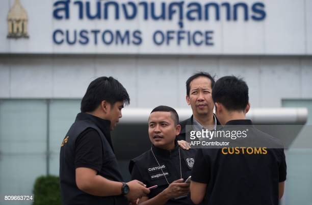 In this June 30 2017 photograph Thai customs agents stand near luxury cars confiscated at a special Free Trade Zone in Bangkok Thailand's role in the...